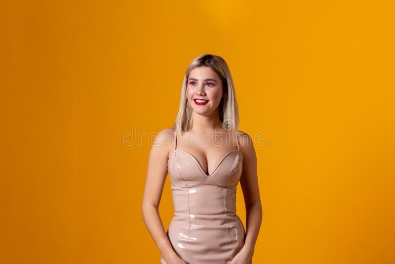 Schönes Modell des blonden Haares, das auf gelbem Hintergrund aufwirft lizenzfreies stockbild