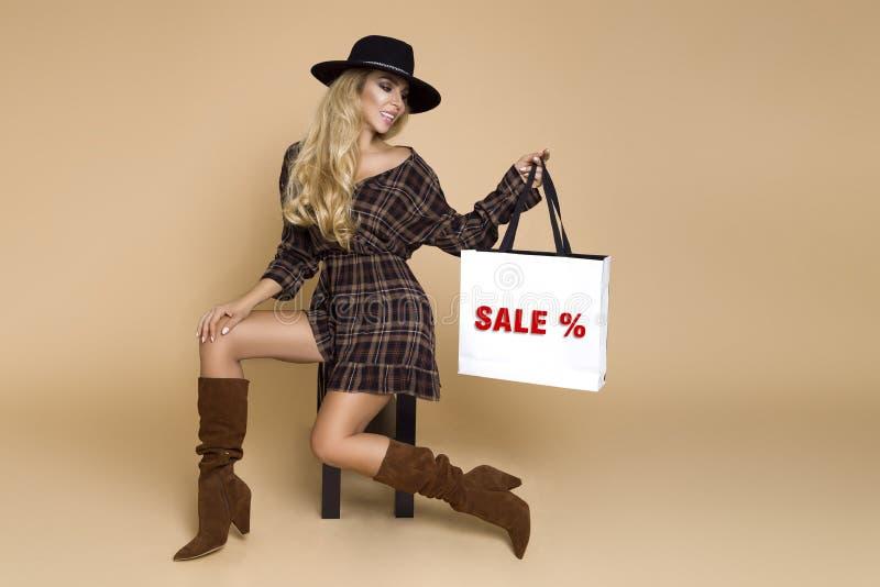 Schönes Modell in einem Hut, in einem Kleid und in Schuhen geht Weibliches Modell hält eine Tasche und geht zum Speicher für eine stockbilder