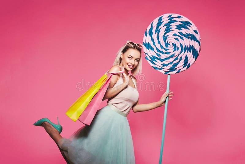 Schönes Modell mit Bonbons am rosa Hintergrund lizenzfreies stockfoto