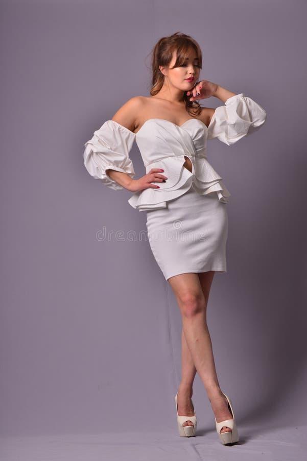 Schönes Modell mit dem langen gelockten Haar, das im eleganten klassischen Abendkleid im Studio aufwirft Hintergrund lizenzfreie stockfotos