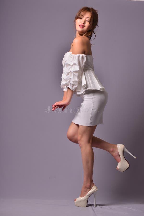 Schönes Modell mit dem langen gelockten Haar, das im eleganten klassischen Abendkleid im Studio aufwirft Hintergrund stockfoto