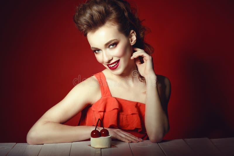 Schönes Modell mit kreativer Frisur und bunte bilden das Sitzen am Holztisch mit köstlichem Kirschgebäck auf ihm stockfotos