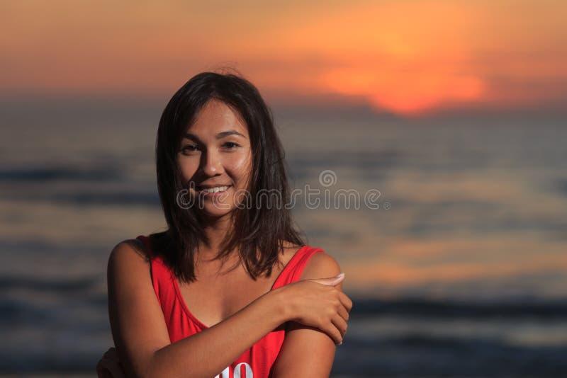 Schönes Modell unter dem Sonnenaufgang an der Küste lizenzfreies stockfoto