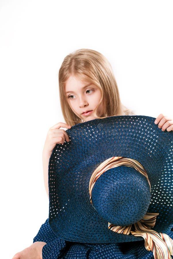 Schönes modernes kleines Mädchen mit dem blonden Haar in einem Hut mit breitem Rand und in einem langen modernen Rock im Studio lizenzfreie stockbilder
