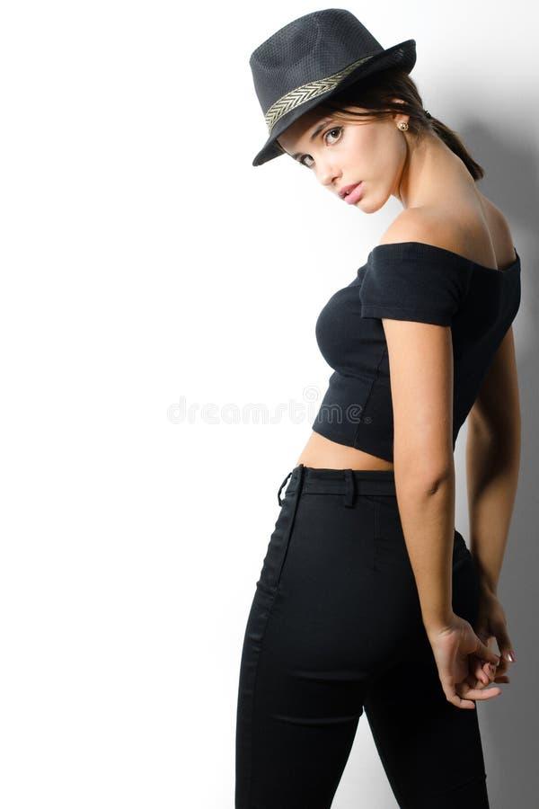 Schönes modernes Mädchen in der schwarzen Kleidung auf weißem Hintergrund stockbilder