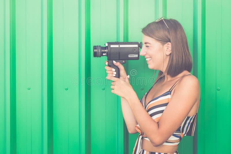 Schönes modernes Mädchen mit alter 8mm Kamera lizenzfreie stockfotos