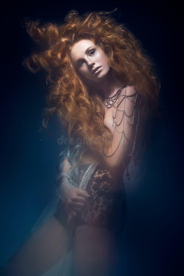 Schönes modernes rothaariges Mädchen im transparenten Kleid, Meerjungfraubild mit kreativer Frisur kräuselt sich Modeschönheitsar stockfotografie