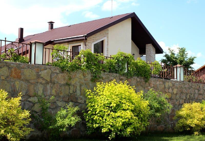 Schönes modernes Wohnlandhaushäuschen mit Zaun und der Landschaftsgestaltung lizenzfreie stockbilder