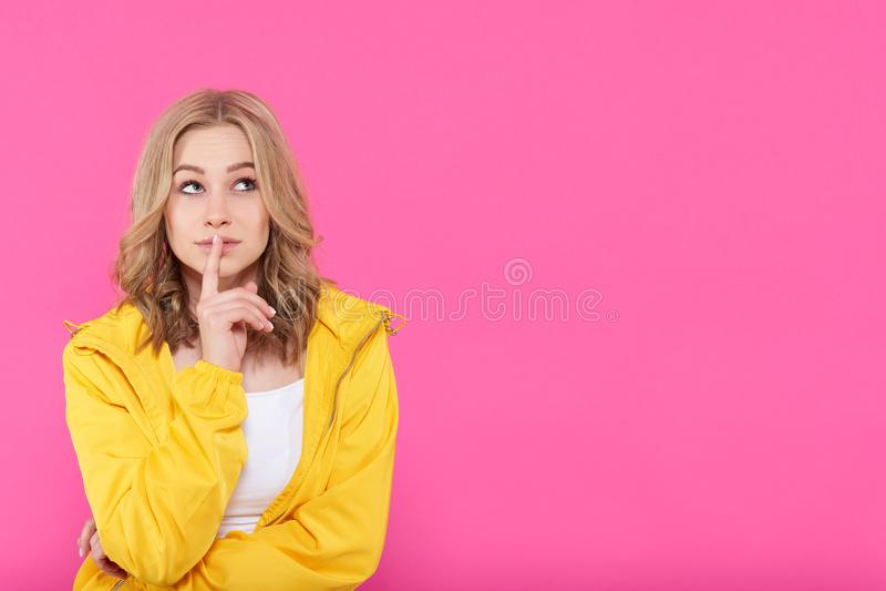Schönes modisches Mädchen in der bunten Kleidung tief in den Gedanken, oben schauend mit dem Finger auf Lippen Attraktives Porträ lizenzfreie stockbilder
