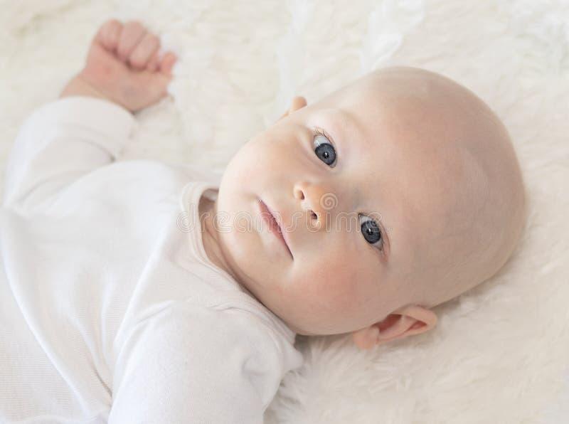 Schönes 6-monatiges Baby gekleidet in weißem u. im Lügen auf der flaumigen weißen Decke, die Kamera betrachtet Lächeln u. glückli lizenzfreies stockfoto