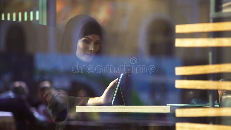 Schönes moslemisches weibliches Sitzen im Café, unter Verwendung des Einkaufsapp auf Tablette, Bankwesen stockfoto