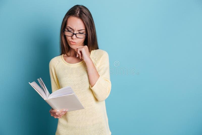 Schönes nachdenkliches Buch des jungen Mädchens Leseüber blauem Hintergrund stockfoto