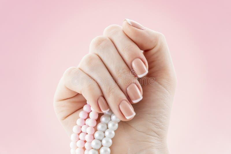 Schönes Nagelstudio der französischen Maniküre Natürlicher Nagelkunstentwurf Frauenhand mit einer Perlenhalskette stockfotos