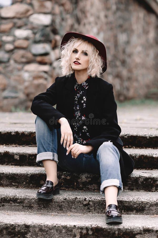 Schönes nettes blondes Mädchen mit dem kurzen gelockten Haar im Mantel und in Hut, die auf Treppe auf der Straße sitzen stockbilder