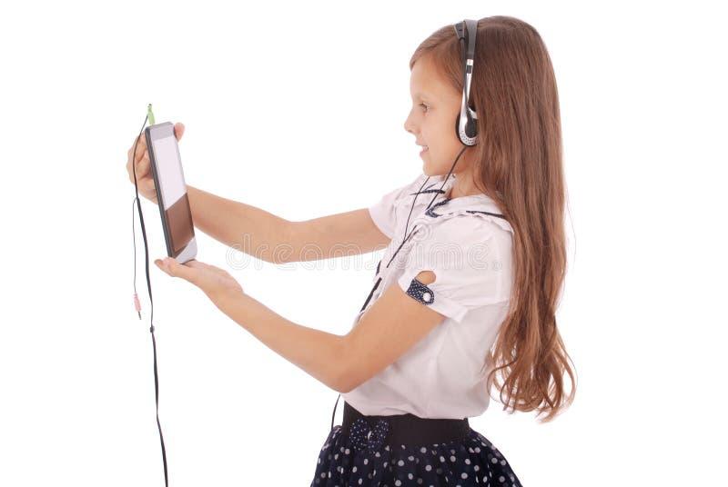 Schönes nettes glückliches junges Mädchen mit Kopfhörern und Tabletten-PC stockbilder