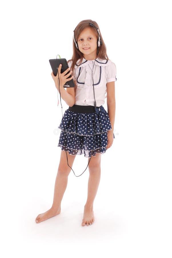 Schönes nettes glückliches junges Mädchen mit Kopfhörern und Tabletten-PC lizenzfreie stockfotos