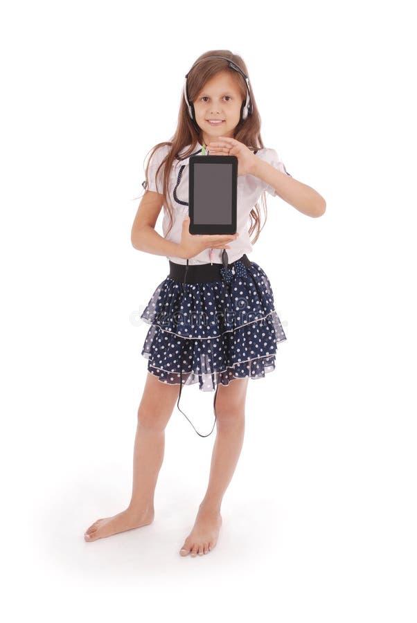 Schönes nettes glückliches junges Mädchen mit Kopfhörern und Tabletten-PC stockfotos