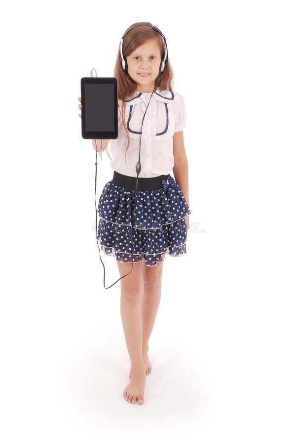 Schönes nettes glückliches junges Mädchen mit Kopfhörern und Tabletten-PC lizenzfreie stockfotografie