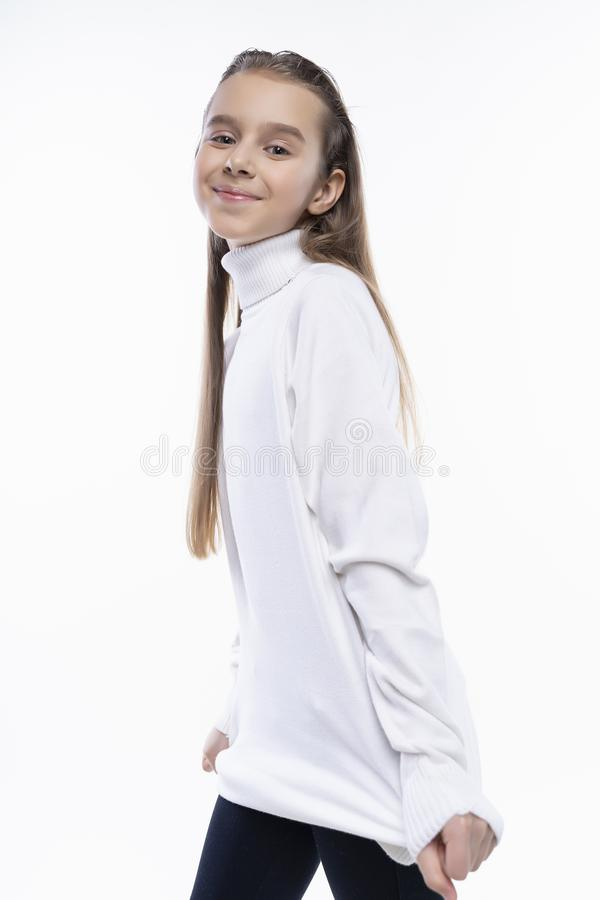 Schönes nettes jugendlich Mädchen, das eine weiße Rollkragenstrickjacke und lächelnde eine Aufstellung der Jeans trägt Getrennt a lizenzfreie stockfotos