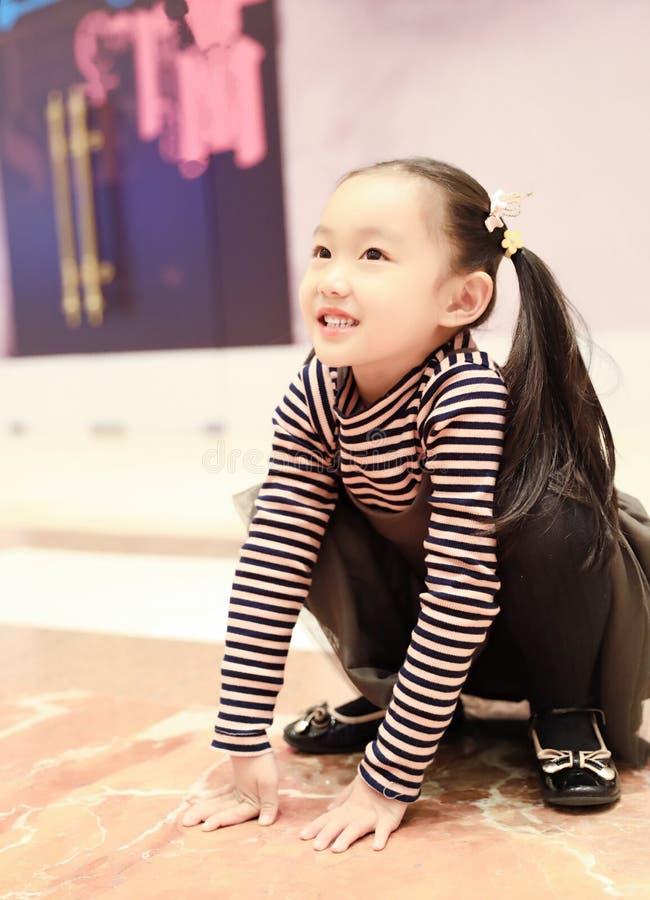 Schönes nettes kleines Mädchen, das Vergnügensboden auf Spielplatz spielt stockfotos