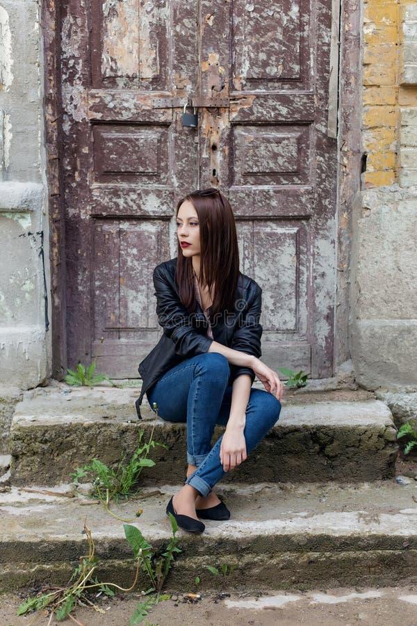 Schönes nettes Modemädchen mit dem dunklen Haar mit Sonnenbrille in einer ledernen schwarzen Jacke, die auf der Treppe das Portal lizenzfreies stockbild