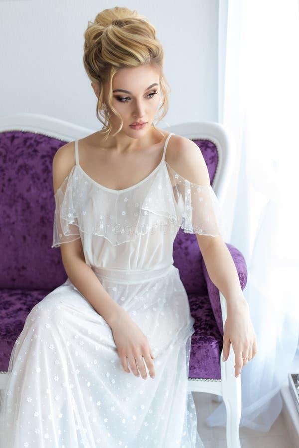 Schönes nettes süßes junges Mädchen in einem helles Kleiderschönen Boudoir mit hellem Make-up smokey mustert mit einem schönen Ab stockbild
