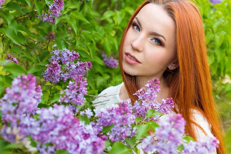 Schönes nettes sexy rothaariges Mädchen mit dem langen Haar in einem weißen Kleid mit einem Blumenstrauß der Flieder in den Hände lizenzfreies stockfoto