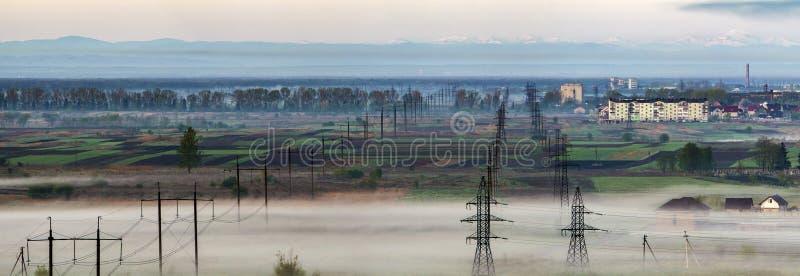 Schönes Panorama von langen elektrischen Hochspannungsleitungsreihen stockbild