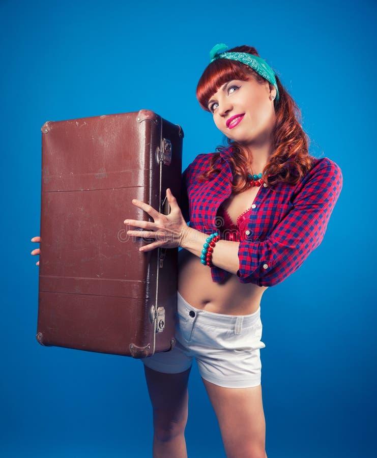 Schönes Pin-up-Girl, das mit Weinlesekoffer gegen Blau aufwirft lizenzfreie stockfotografie