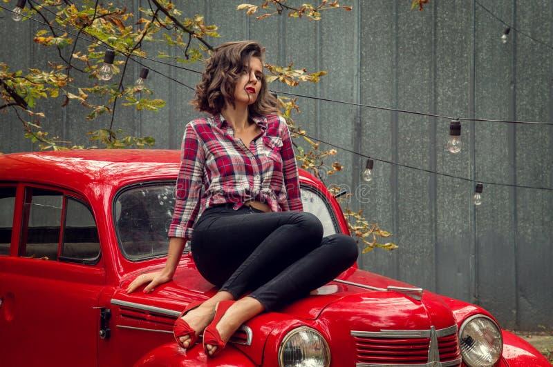 Schönes Pin-up-Girl in den Jeans und in einer Aufstellung des karierten Hemds, sitzend auf der Haube eines roten Retro- Autos lizenzfreie stockfotos