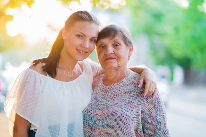 Schönes Porträt der Großmutter und ihre Enkelin, die auf Sommerstraße im Freien steht Goldene Stunde, Sonnenaufflackern Mädchen lizenzfreie stockfotos