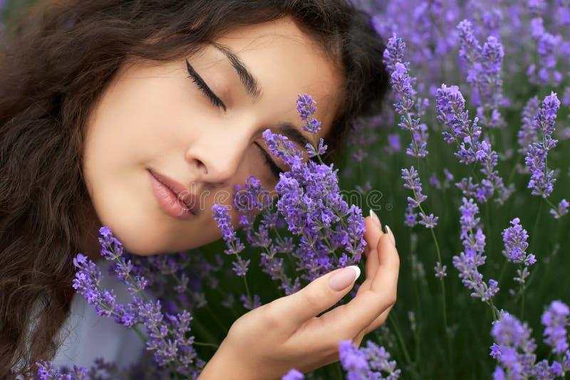Schönes Porträt der jungen Frau auf Lavendel blüht Hintergrund, Gesichtsnahaufnahme lizenzfreies stockbild