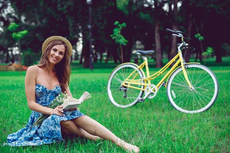 Schönes Porträt der jungen Frau, das ein Buch mit Fahrrad im Park liest stockfoto