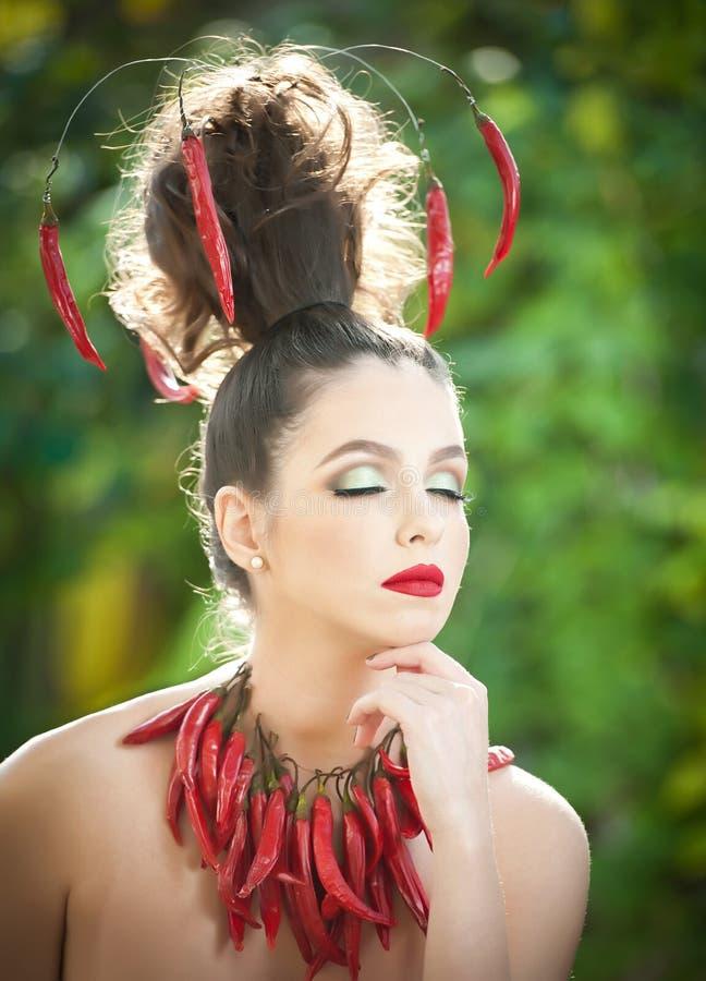 Schönes Porträt der jungen Frau mit glühenden würzigen Pfeffern um den Hals und im Haar, Mode-Modell mit kreativem Lebensmittelge lizenzfreie stockbilder