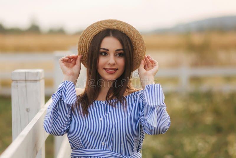 Schönes Porträt der netten schwangeren Frau im blauen Kleid und in der Strickmütze Damenl?cheln stockbild