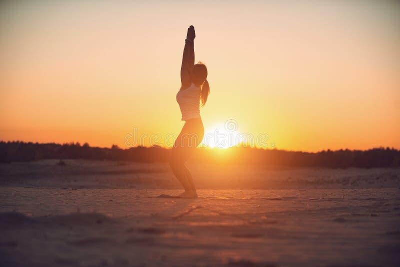 Schönes Praxisyoga asana Utkatasana - Stuhlhaltung der jungen Frau in der Wüste bei Sonnenuntergang stockbild