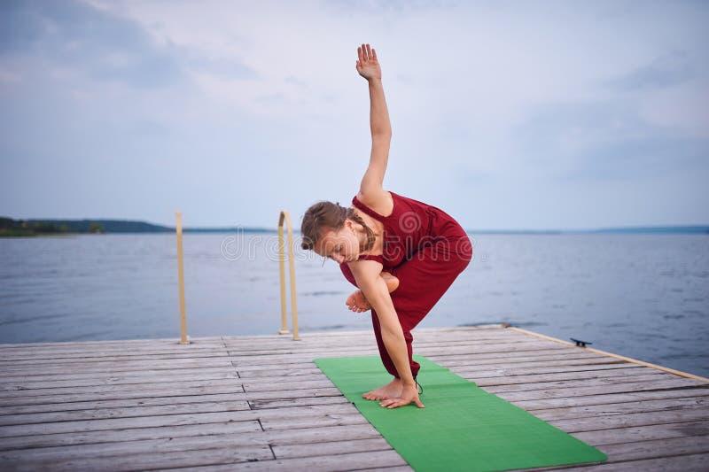 Schönes Praxisyoga der jungen Frau auf der hölzernen Plattform nahe dem See stockfotografie