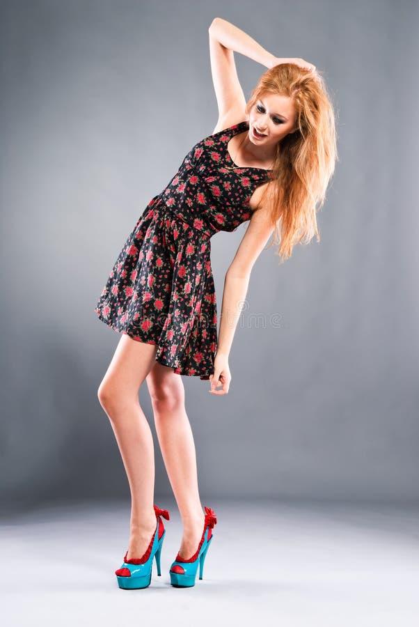 Schönes red-haired Mädchen auf grauem Hintergrund stockfotografie
