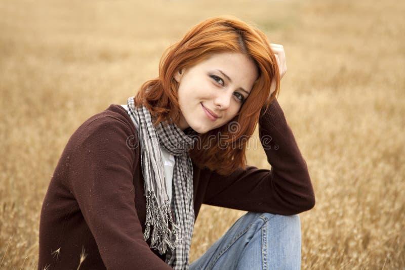 Schönes red-haired Mädchen am gelben Herbstgras. lizenzfreies stockfoto