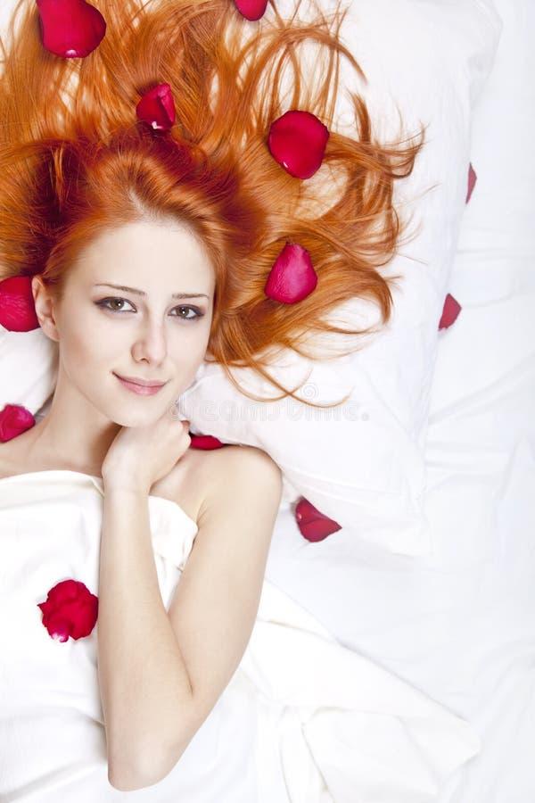 Schönes red-haired Mädchen im Bett mit dem rosafarbenen Blumenblatt. stockfotos