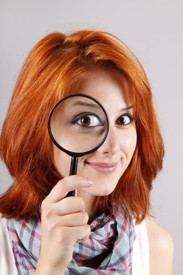 Schönes red-haired Mädchen mit Lupe lizenzfreie stockbilder