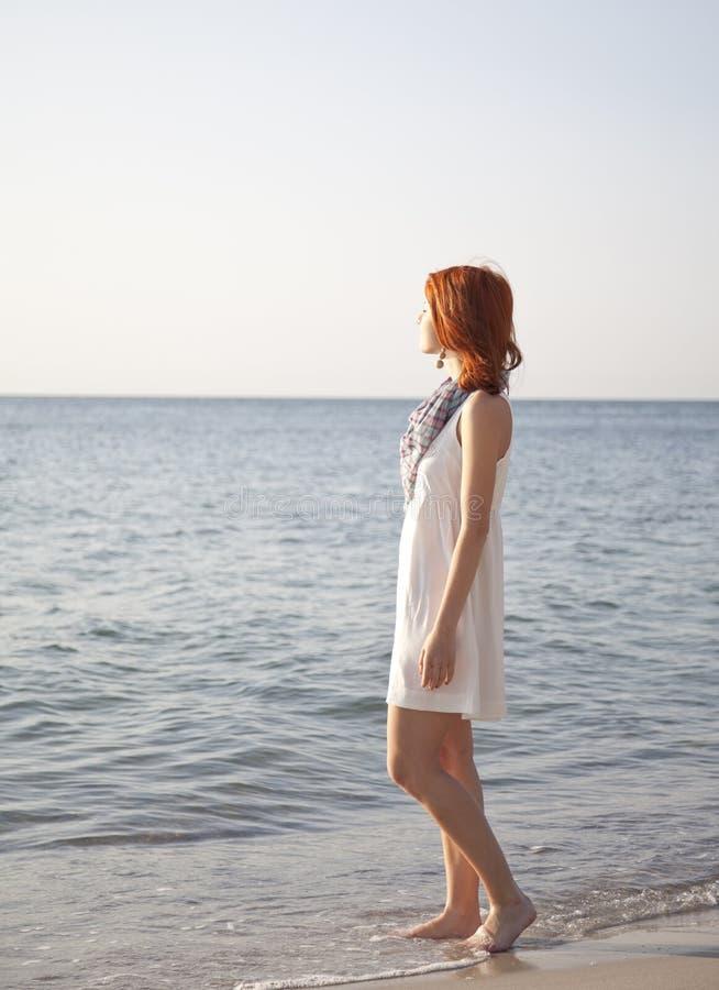 Schönes red-haired Mädchen am Sonnenaufgang auf dem Strand. stockbilder