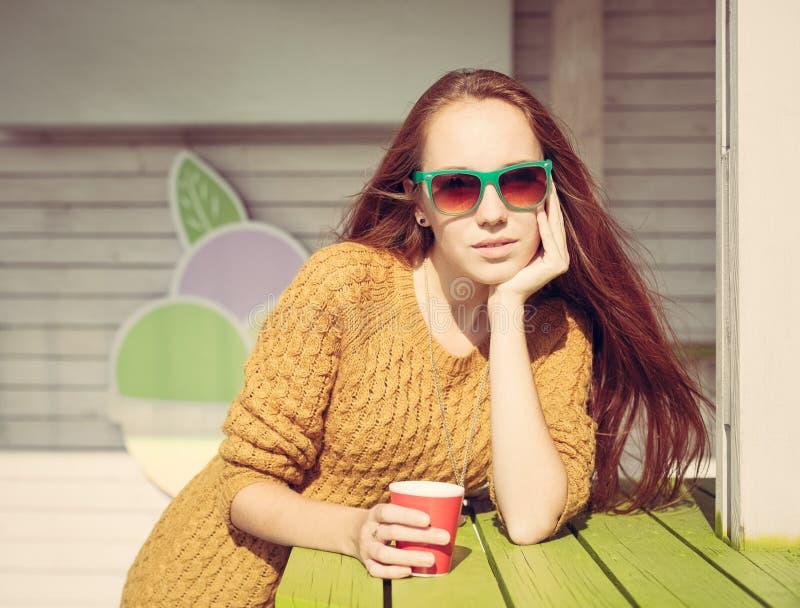 Schönes redheaded Mädchen in der Sonnenbrille für Cafétabelle des Sommers im Freien lizenzfreie stockbilder
