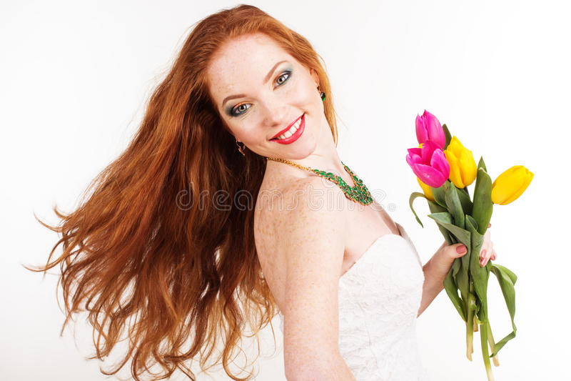 Schönes redheaded Mädchen hält Tulpen stockbilder