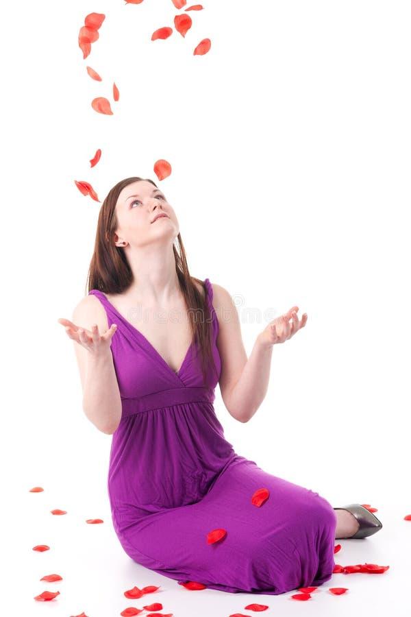 Schönes Redheadmädchen mit den rosafarbenen Blumenblättern lizenzfreie stockfotos