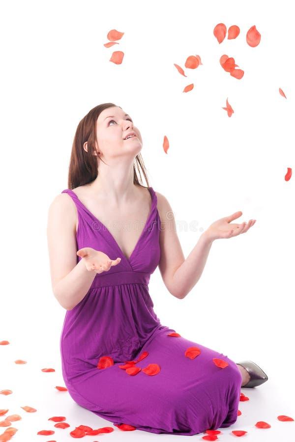 Schönes Redheadmädchen mit den rosafarbenen Blumenblättern lizenzfreies stockbild