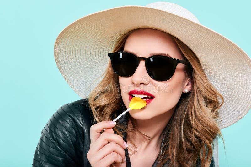 Schönes Rockermädchen in der Lederjacke und in der Sonnenbrille mit Herzen formte Lutscher Attraktives kühles Modeporträt der jun stockbilder