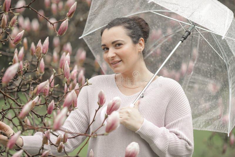 Schönes romantisches rotes behaartes Mädchen des Frühlinges im weißen Spitzekleid und -jeans, die nahe blühendem Baum mit transpa lizenzfreie stockbilder