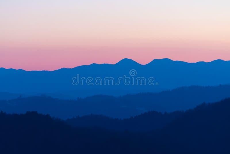 Schönes Rosa und blaue Farbnuancen des Dämmerungshimmels und -hügel nach Sonnenuntergang stockfotografie