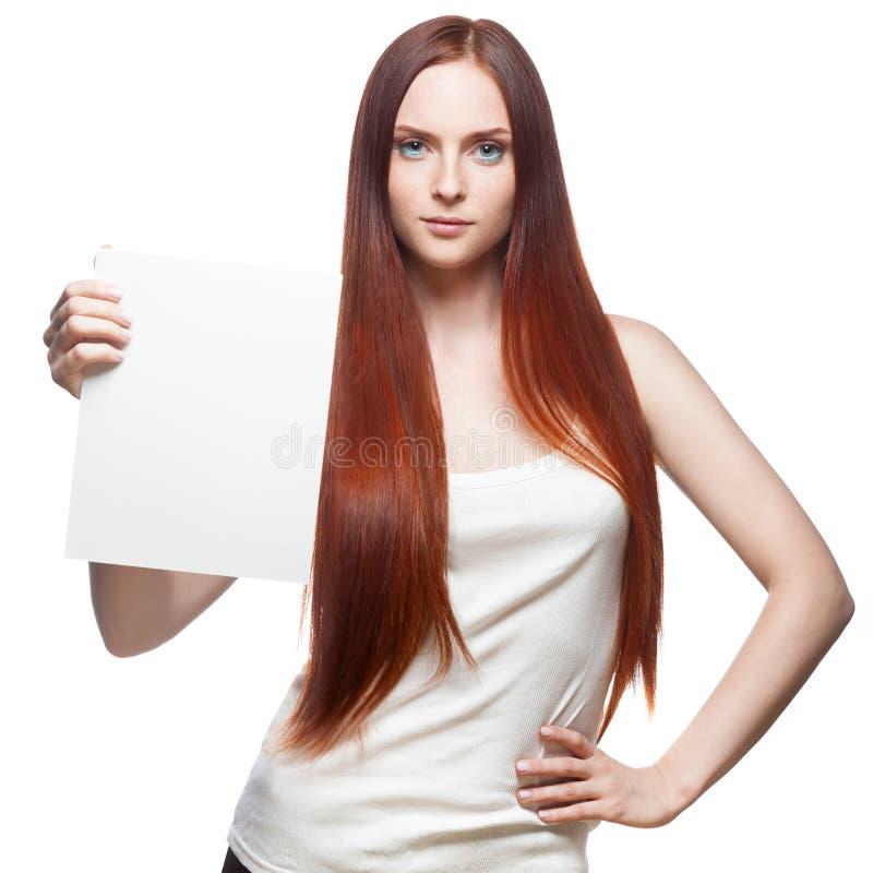 Schönes rotes behaartes Mädchen, das Zeichen anhält lizenzfreies stockfoto